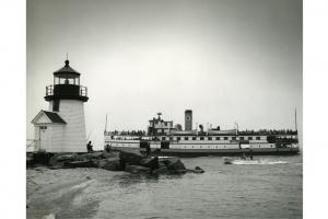 Steamship Nobska rounding Brant Point outbound; excellent view of the lighthouse and fishermen in the foreground.