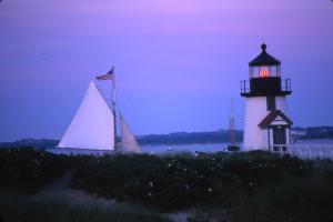 Sloop Endeavour passing Brant Point lighthouse at dusk