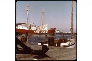 Lightship Nantucket docked at Steamboat Wharf, with Brant Point lighthouse in the distance.