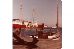 The Nantucket lightship docked at Steamboat Wharf, with the U.S. Coast Guard boat house and Brant Point lighthouse in th