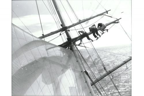 Three members of the crew on a spar above the deck of the Brig Yankee, 1959.