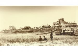 View of the train below the south bluff of Siasconset with hotels and houses in the background, circa 1900.