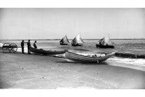 Fishermen and boats on the beach, circa 1890.